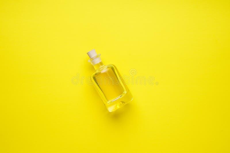 Den lilla flaskan av solros-kärnar ur olja på den gula lägenheten arkivfoton