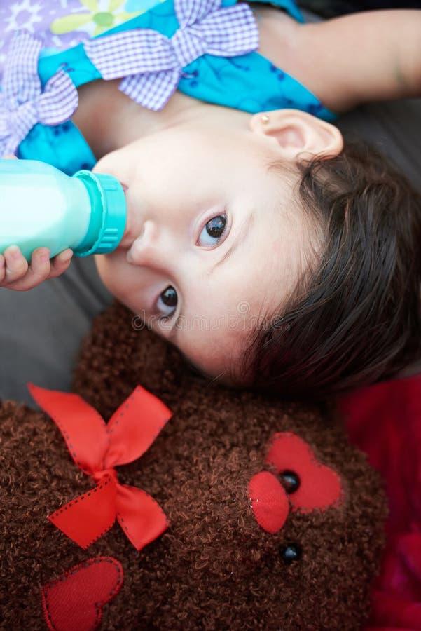 Den lilla flickadrinken mjölkar royaltyfri bild