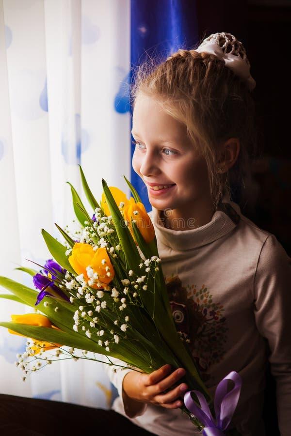 Den lilla flickan för det härliga barnet med buketten av tulpanblommor hemma nära fönstret, framlägger för mors dag Gåva överrask royaltyfri fotografi