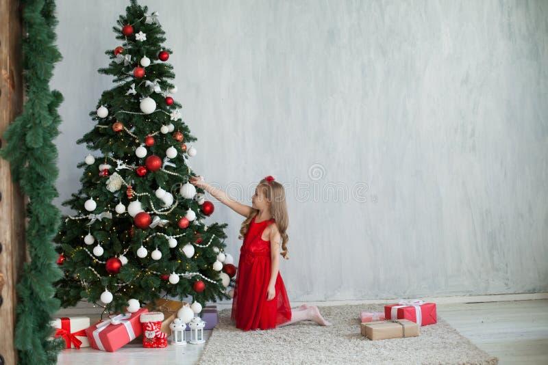 Den lilla flickan i en röd klänning dekoreras med ferie för nytt år för julgåvor royaltyfria bilder