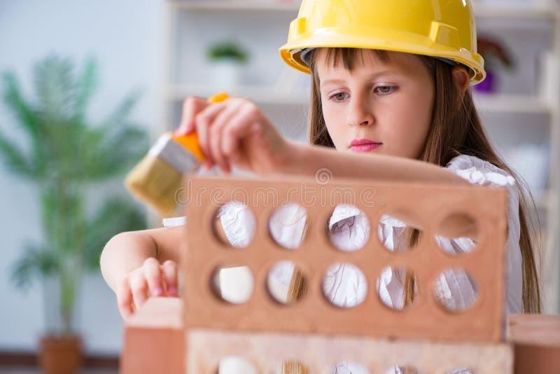 Den lilla flickan som spelar med tegelstenar fotografering för bildbyråer
