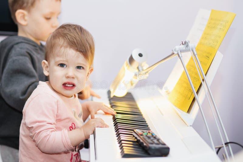 Den lilla flickan tycker om att spela den elektriska pianosyntet för fet arkivfoto