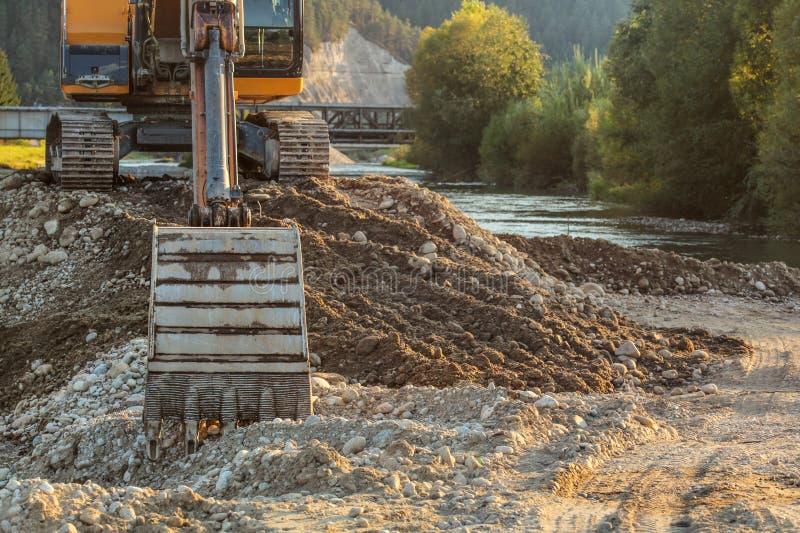 Den lilla gula grävskopan på högen av vaggar och stenar bredvid floden, detalj på grävarehinken på jordning Konstruktion på flods arkivfoto