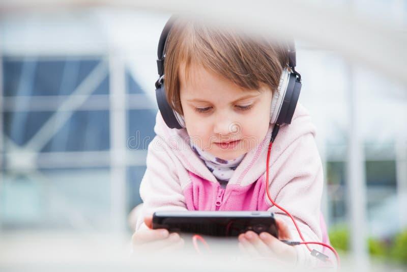 Den lilla gulliga barnflickan som bär hörlurar, lyssnar den fria ljudsignal kursen för online-rengöringsduken utomhus royaltyfria bilder