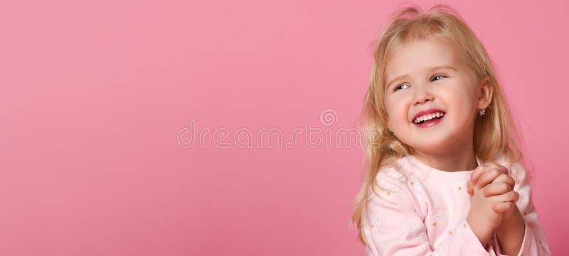 Den lilla gulliga flickabarnblondinen i en rosa dr?kt ?r blyg p? en rosa bakgrund royaltyfri foto