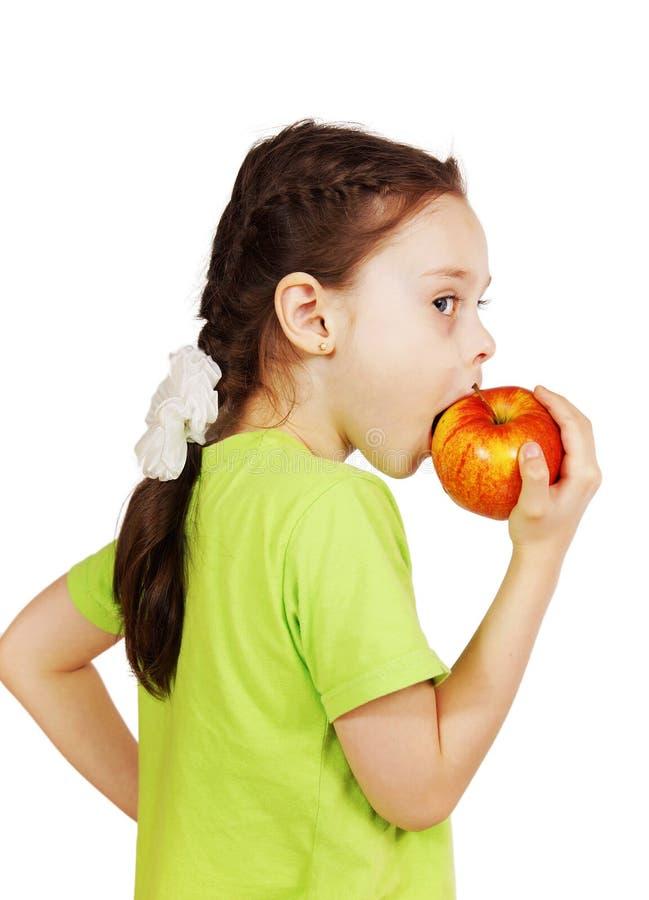 Den lilla gulliga flickan biter ett stort rött äpple royaltyfri fotografi