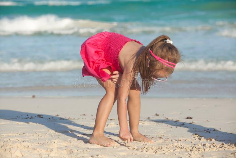 Den lilla gulliga flickan drar på den vita sanden på fotografering för bildbyråer