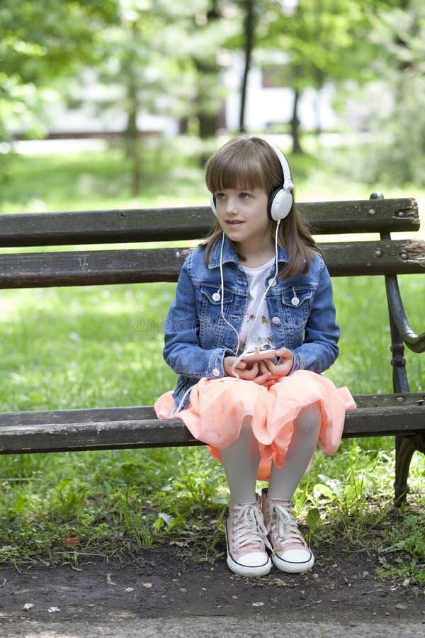 Den lilla gulliga flickan i ett kjolsammanträde på en parkerabänk och tycker om royaltyfri bild