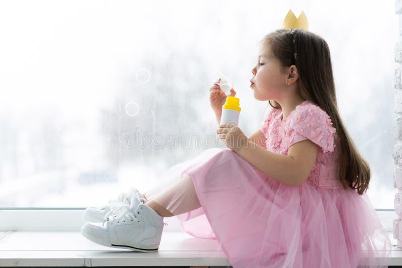Den lilla gulliga flickan i härlig klänning sitter nära fönstret hemma och blåser såpbubblor royaltyfri fotografi