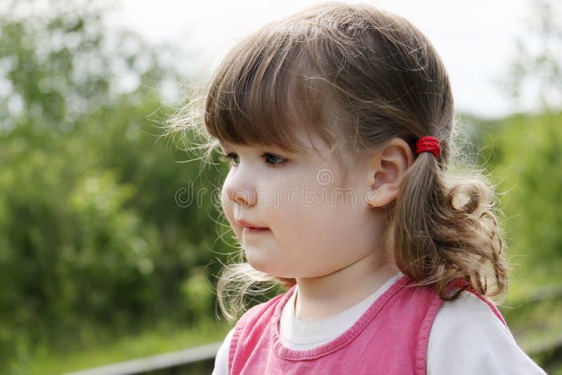 Den lilla gulliga flickan ser bort på sommar D royaltyfri foto