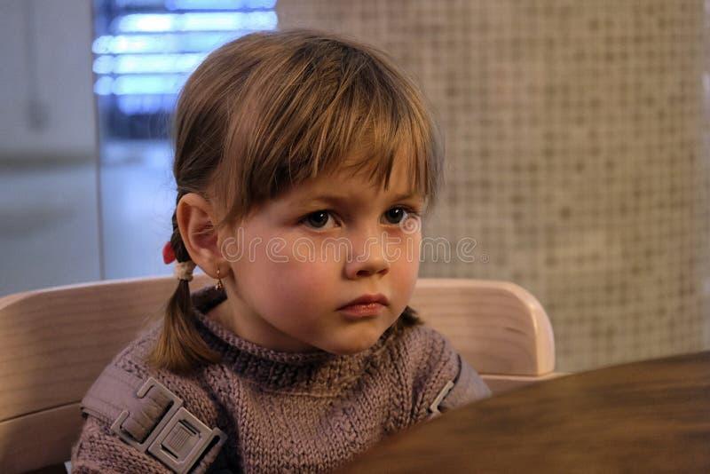 Den lilla gulliga flickan ser hänsynsfullt arkivbild