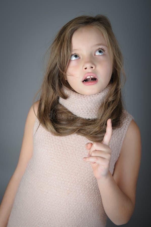 Den lilla gulliga flickan som ser upp och, visar upp royaltyfri fotografi