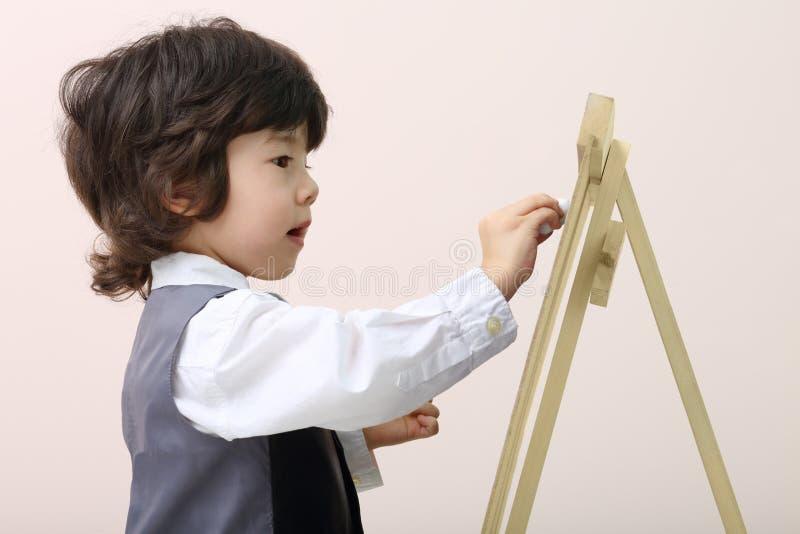 Den lilla gulliga koncentrerade pojken drar vid krita på den svart tavlan royaltyfria bilder
