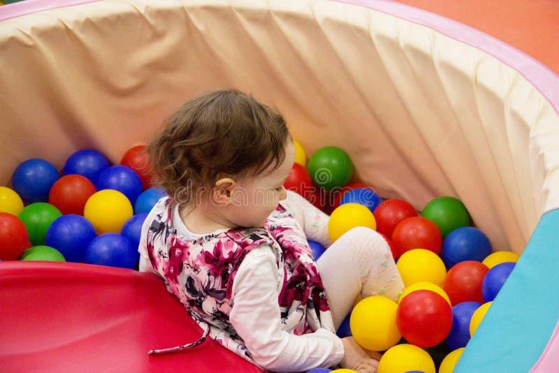 Den lilla gulliga leendeflickan spelar i bollar för en torr pöl Lekrum Lycka royaltyfria bilder