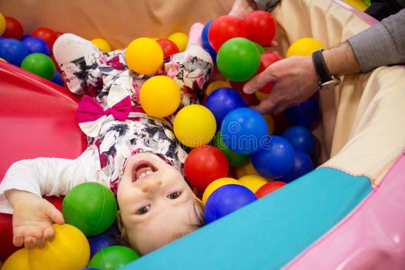 Den lilla gulliga leendeflickan spelar i bollar för en torr pöl Lekrum Lycka hand för fader` s i bakgrunden arkivfoton