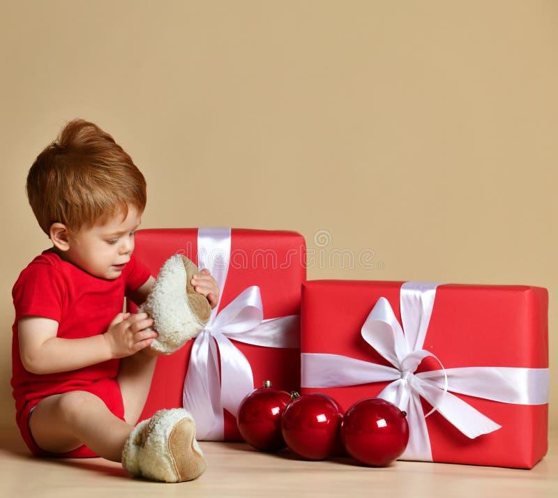 Den lilla gulliga litet barnpojken sitter bland iklädda gåvor en röd kroppdräkt och varma gymnastikskor fotografering för bildbyråer