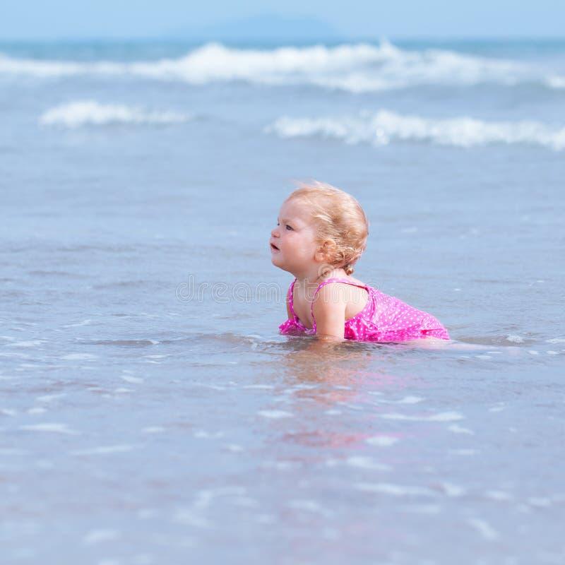 Den lilla gulliga lyckliga flickan badar i havet, Italien som är utomhus- arkivbild