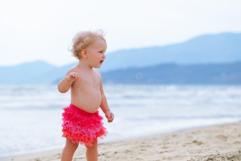 Den lilla gulliga lyckliga flickan badar i havet, Italien som är utomhus- royaltyfri bild