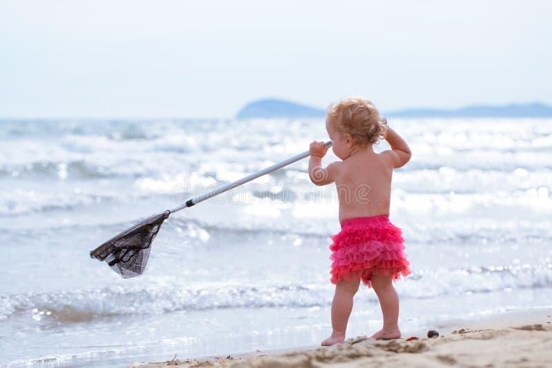 Den lilla gulliga lyckliga flickan badar i havet, Italien som är utomhus- royaltyfria bilder