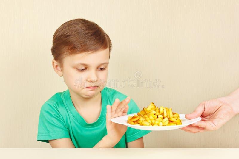 Den lilla gulliga olyckliga pojken vägrar att äta franska småfiskar arkivfoto