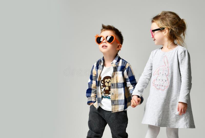 Den lilla gulliga pojkeflickahållen räcker att spela på grå bakgrund arkivfoto