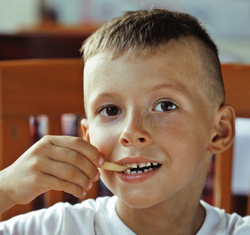 Den lilla gulliga pojken 6 gamla år med hamburgaren och fransman steker maki arkivfoto