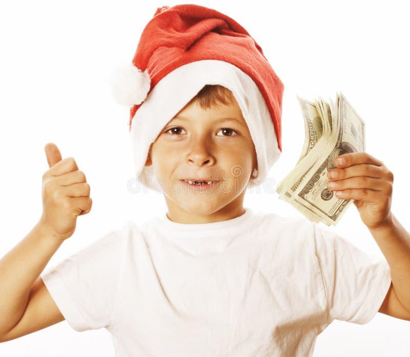 Den lilla gulliga pojken i santas den röda hatten som isoleras med kontanta amerikanska dollar, tummar upp lycklig ungeferieberöm fotografering för bildbyråer