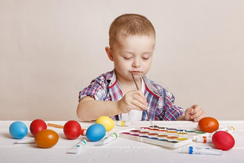 Den lilla gulliga pojken målar färgrika påskägg royaltyfria foton