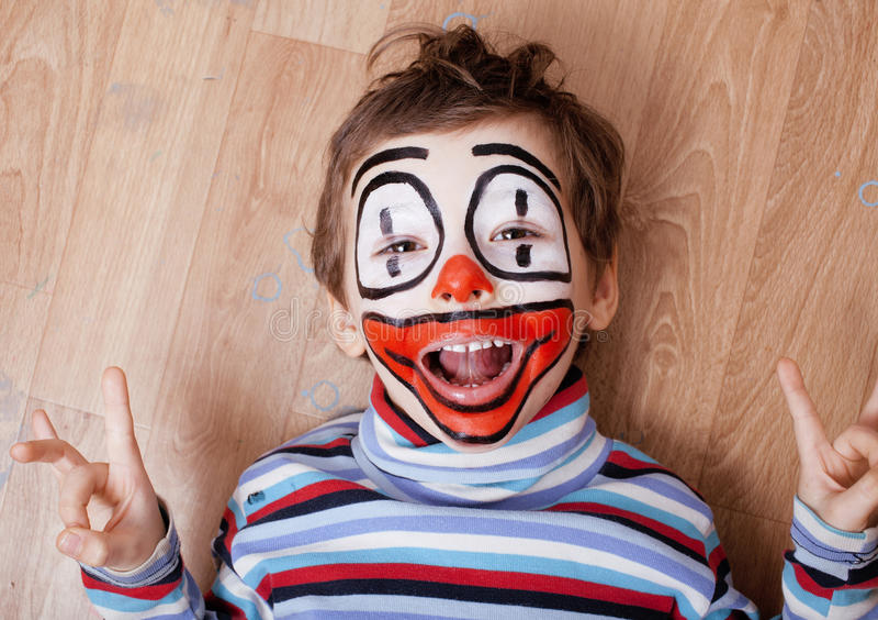 Den lilla gulliga pojken med facepaint som clown, pantomimic uttryck stänger sig upp arkivfoto