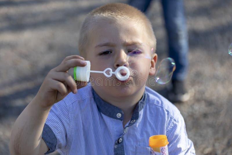 Den lilla gulliga pojken som blåser bubblor i, parkerar royaltyfri foto