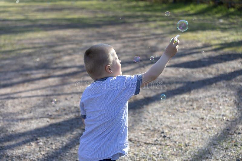 Den lilla gulliga pojken som bl?ser bubblor i, parkerar fotografering för bildbyråer