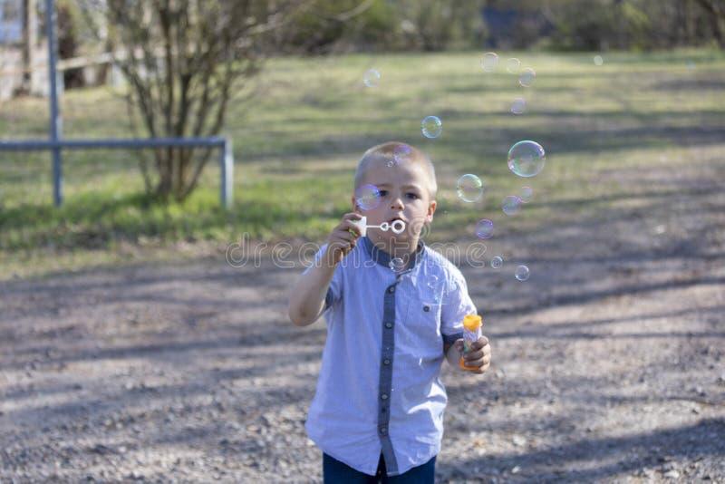 Den lilla gulliga pojken som bl?ser bubblor i, parkerar royaltyfri bild