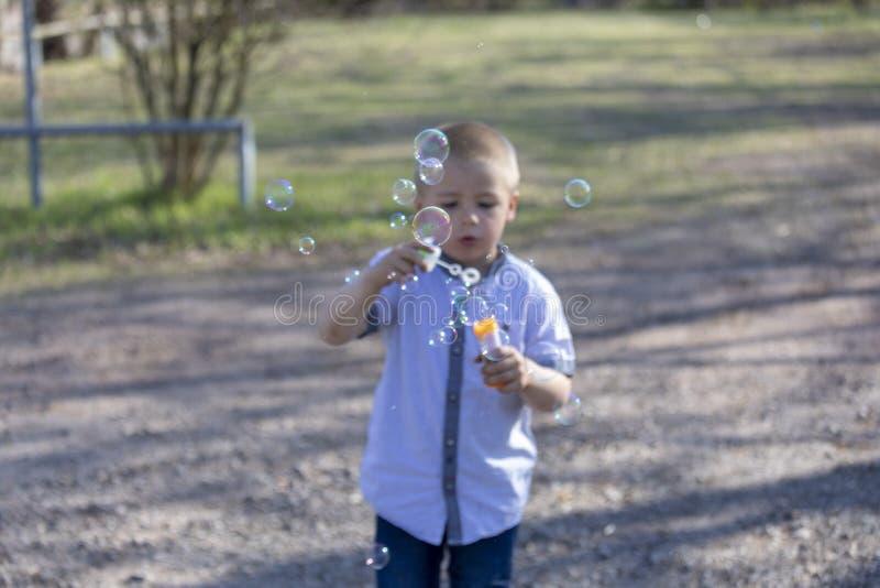 Den lilla gulliga pojken som bl?ser bubblor i, parkerar arkivbilder