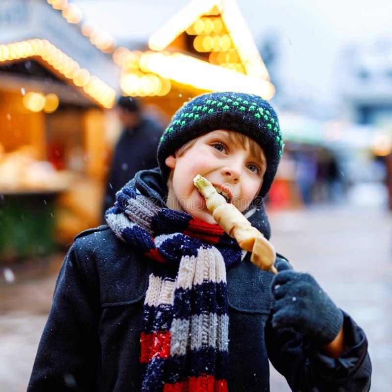 Den lilla gulliga ungepojken som ?ter t?ckt vit choklad, b?r frukt p? stekn?len p? traditionell tysk julmarknad lyckligt barn arkivfoton