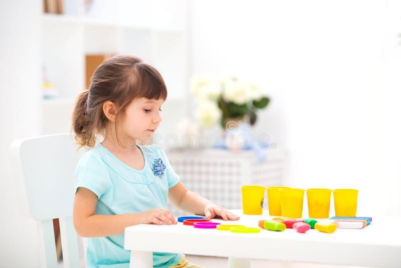 Den lilla härliga flickan hugger från plasticine på tabellen i inre Barns utveckling och fin motorexpertis Barn` s royaltyfria foton