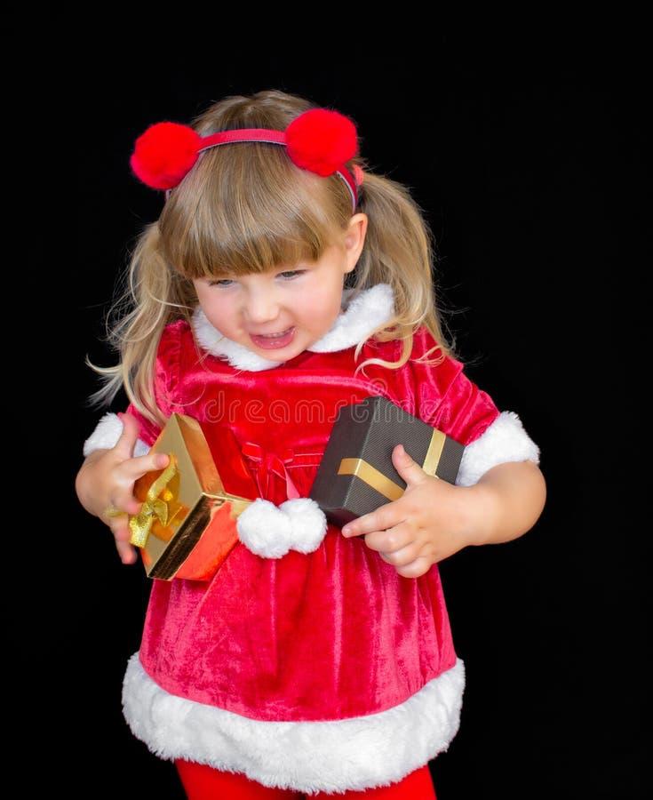 Den lilla härliga flickan i en juljultomtendräkt, med pälsbollar på hennes huvud, rymmer gåvor i hennes händer och jublar royaltyfri bild