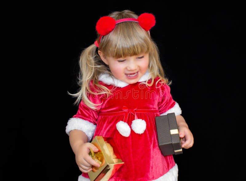 Den lilla härliga flickan i en juljultomtendräkt, med pälsbollar på hennes huvud, rymmer gåvor i hennes händer och jublar fotografering för bildbyråer