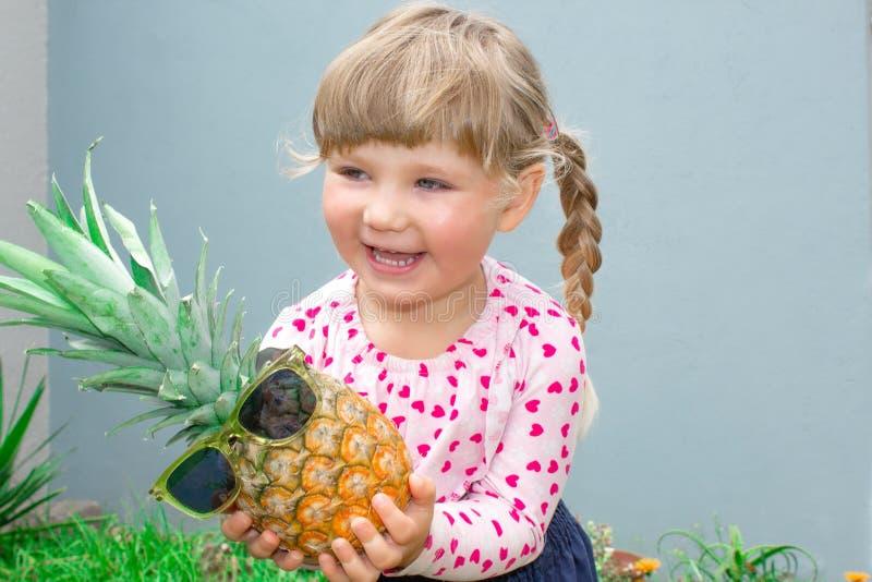 Den lilla härliga flickan ler, skrattar och rymmer glatt i handananas i exponeringsglas I det trädgårds- utomhus royaltyfria foton