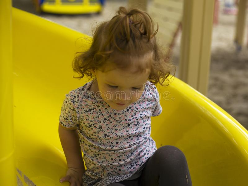 Den lilla härliga flickan spelas på lekplatsen royaltyfri foto