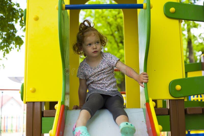 Den lilla härliga flickan spelas på lekplatsen royaltyfria foton