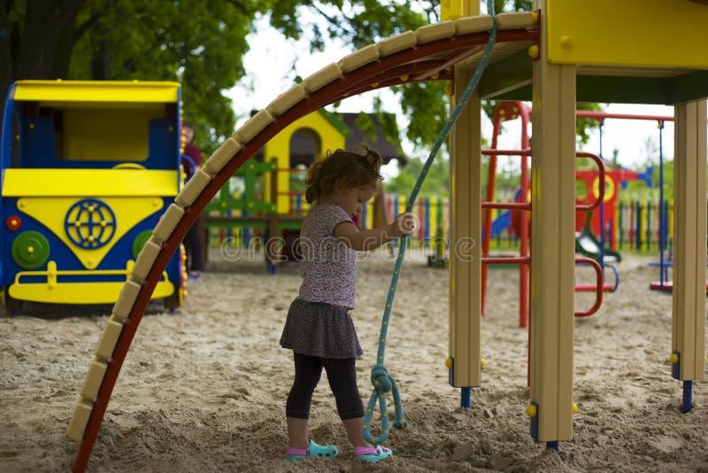 Den lilla härliga flickan spelas på lekplatsen arkivbild