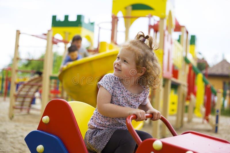 Den lilla härliga flickan spelas på lekplatsen royaltyfri bild