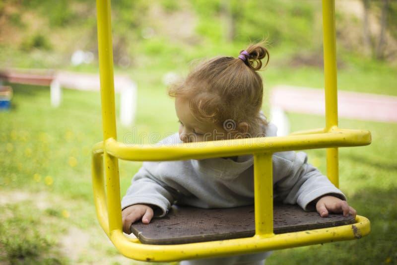 Den lilla härliga rödhåriga flickan hängde på en gunga, behandla som ett barn lekar på en gunga på lekplatsen royaltyfri fotografi