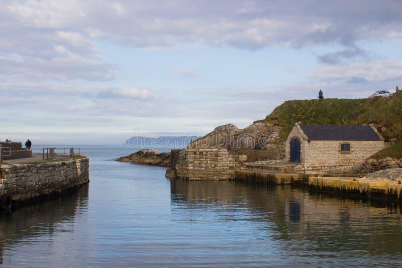 Den lilla hamnen på Ballintoy på den norr Antrim kusten av nordligt - Irland med dess sten byggde sjöboden på en dag i vår royaltyfri bild