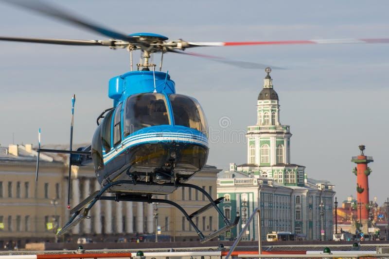 Den lilla helikoptern tar av från helipaden i St Petersburg, mot bakgrunden av Kunstkameraen, pilen av Vasilyen royaltyfri fotografi