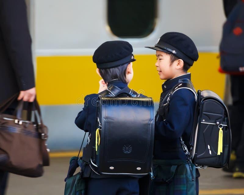 Den lilla japanska studenten väntade på ett drev till skolan royaltyfri foto