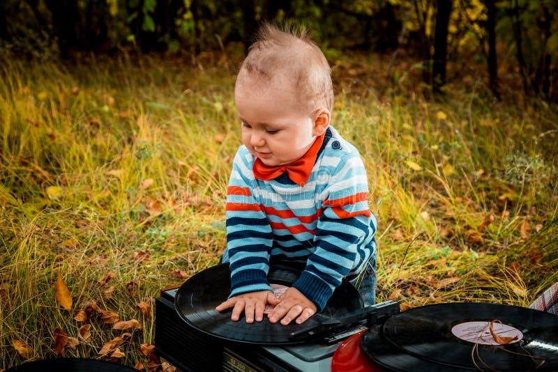 Den lilla knubbiga ungen som spelar med retro musik, antecknar utomhus arkivbilder