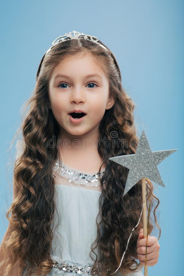 Den lilla kvinnliga prinsessan för det lilla barnet bär kronan, och klänningen, rymmer trollspöet, har mörkt lockigt hår poserar  arkivfoton