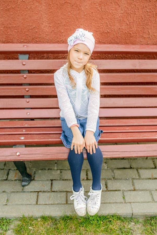 Den lilla le flickan i ett lock sitter på bänk arkivfoto