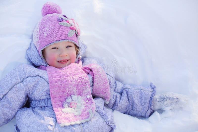 Den lilla le flickan i halsduk och hatt ligger på snö på vintern arkivfoto